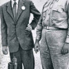 JULIUS ROBERT OPPENHEIMER mit General LESLIE R. GROVES, dem verantwortlichen Militär für den Bau der Bombe, am Rand des Kraters der Versuchsexplosion in der Wüste von New Mexico (1945)